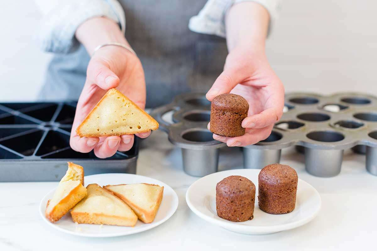A baker holding up madeleines baked a in mini scone pan and a mini popover pan
