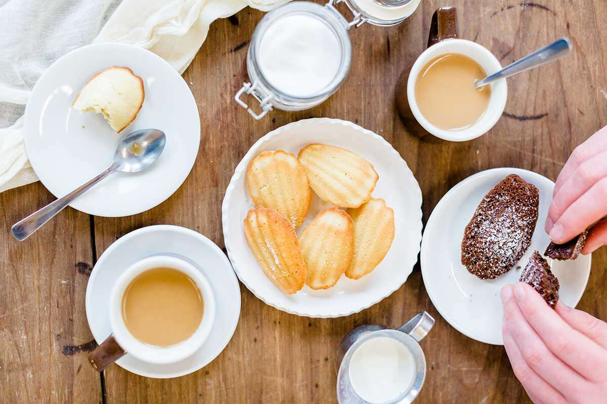 A plate of vanilla madeleines on a wooden table with a few cups of coffee, tea, and small plates