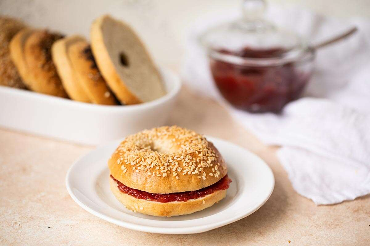 A homemade sesame bagel on a plate with strawberry jam
