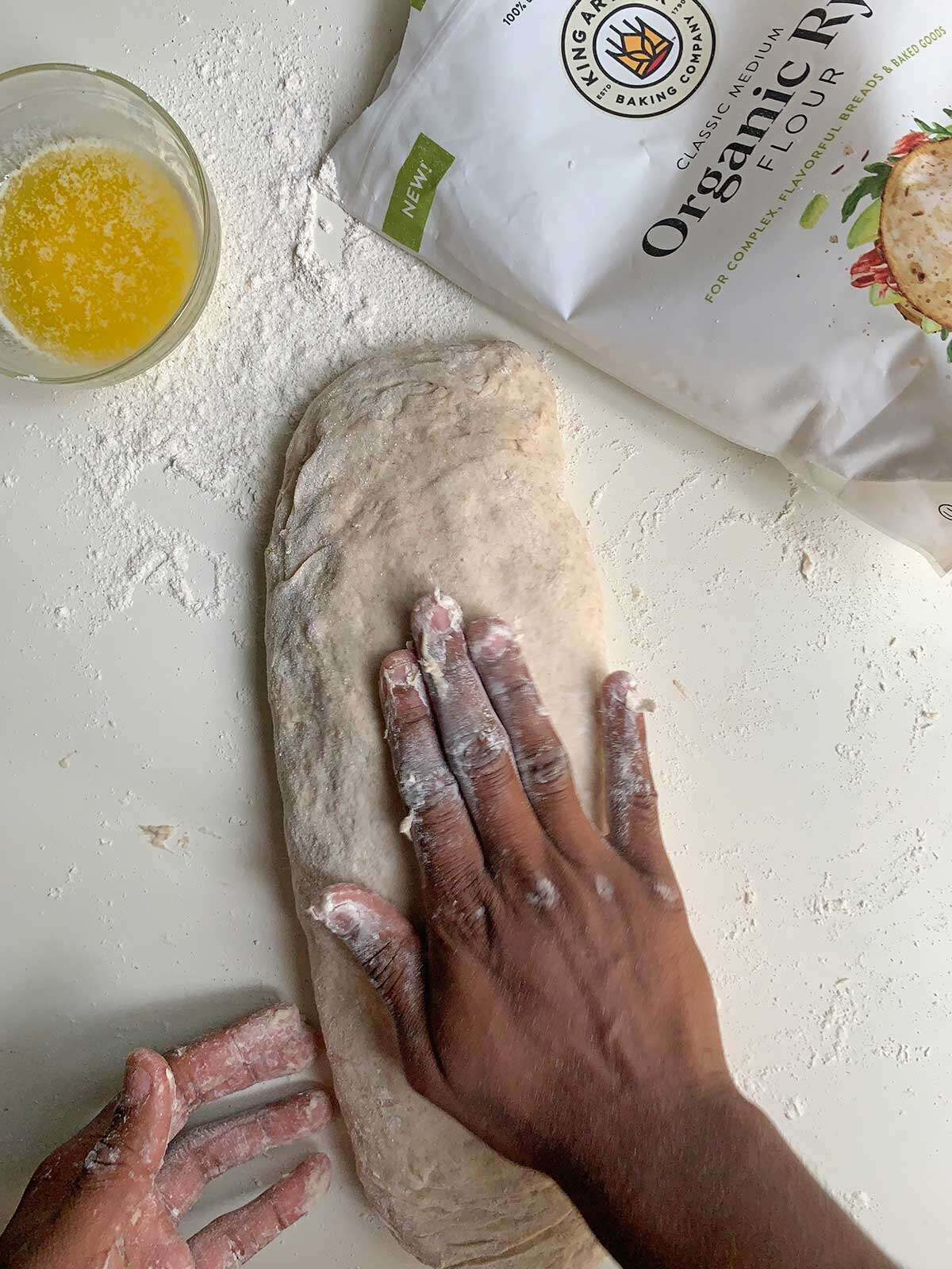Hands shaping the focaccia dough