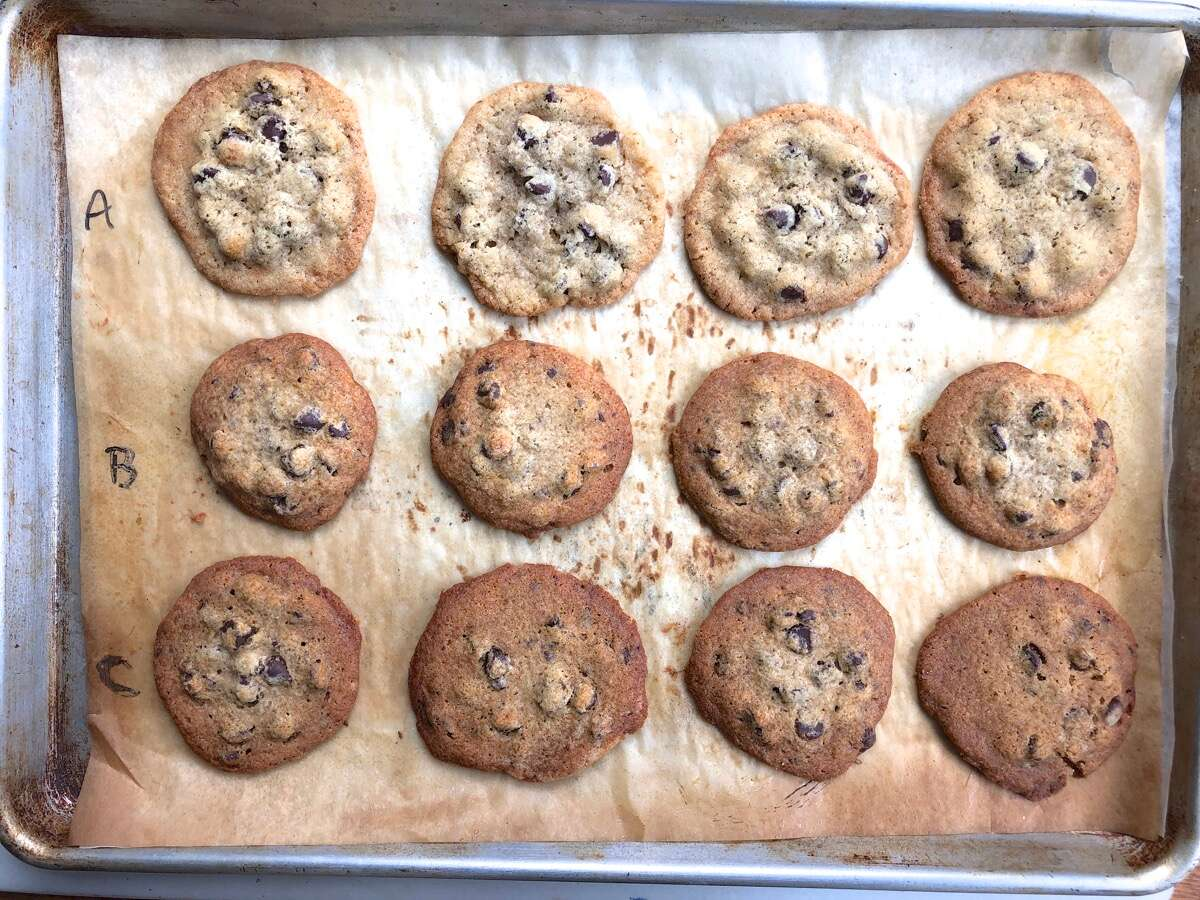 Chocolate chip cookies on a baking sheet; some made with Baking Sugar Alternative, some with regular cane sugar.