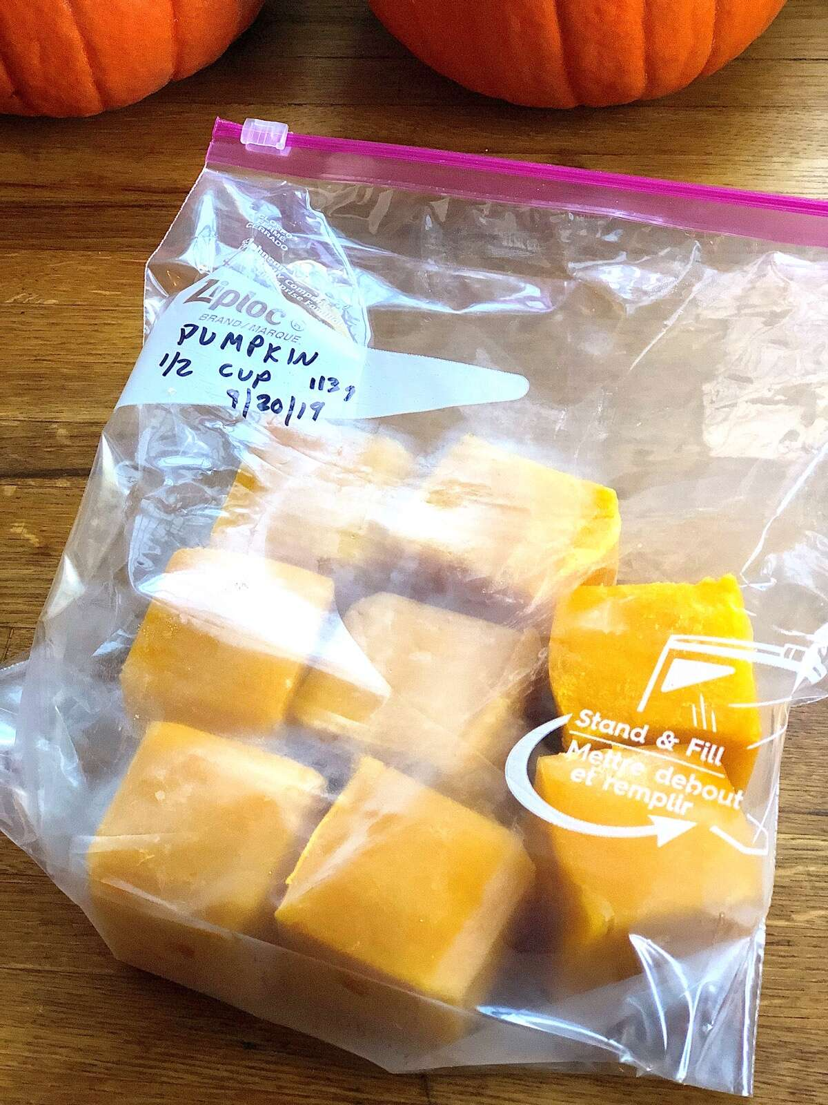Homemade pumpkin purée frozen in cubes, placed in a labeled freezer bag