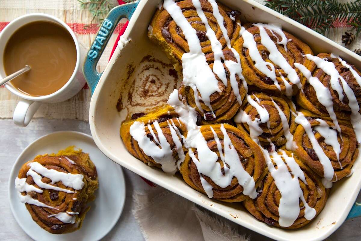 Cinnamon swirl pumpkin rolls iced with confectioners' sugar icing, ready to serve