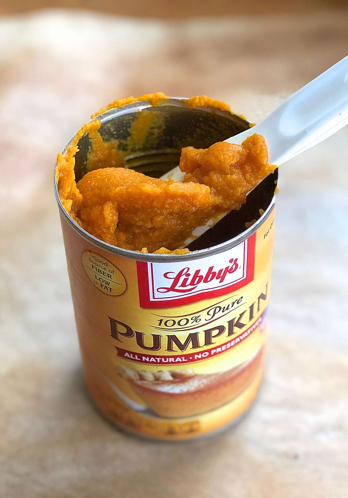 Pumpkin purée being spooned out of half-empty pumpkin can