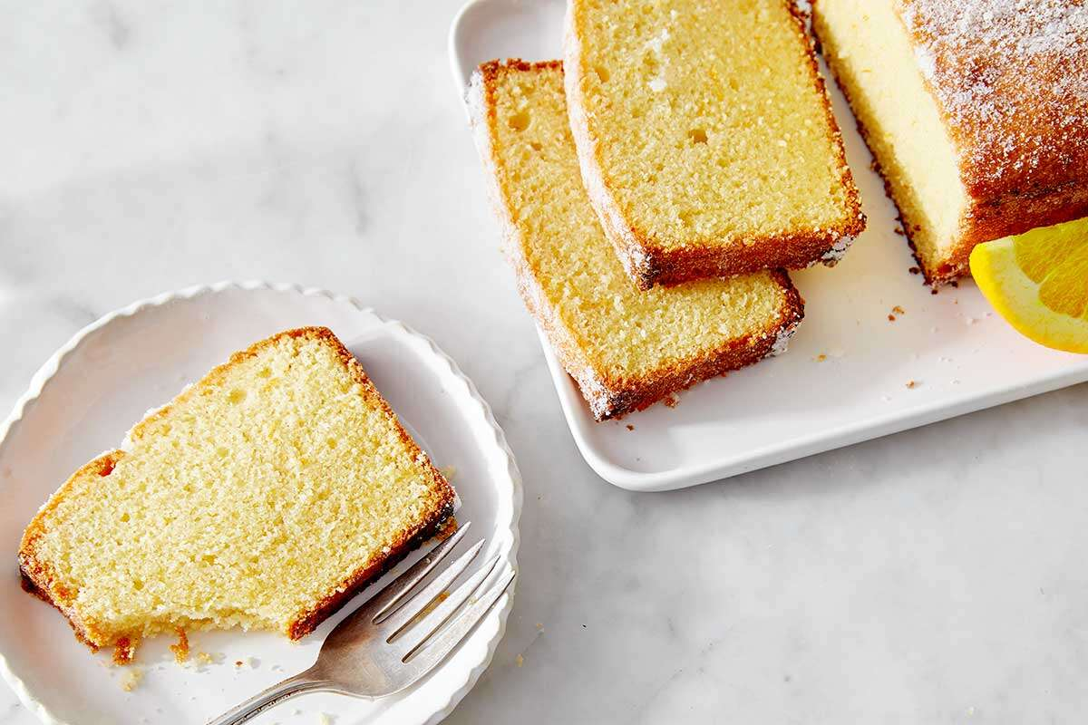 A loaf of lemon pound cake with a few slices on plates