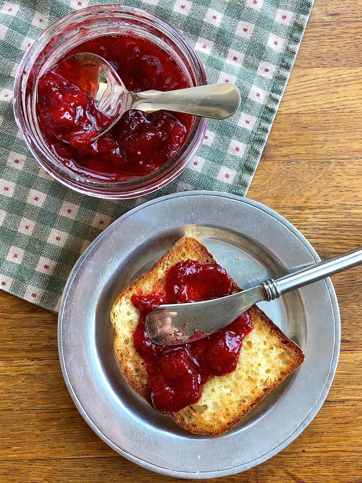 Slice of buttered toast with strawberry jam, jar of jam with spoon.