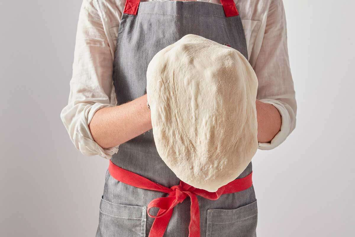 Standing baker shaping dough into a pizza shape
