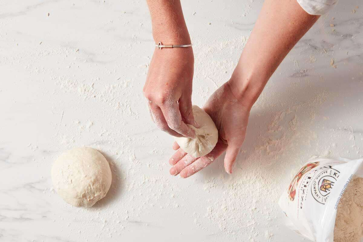 Hands cupping a shaped pouch of dough