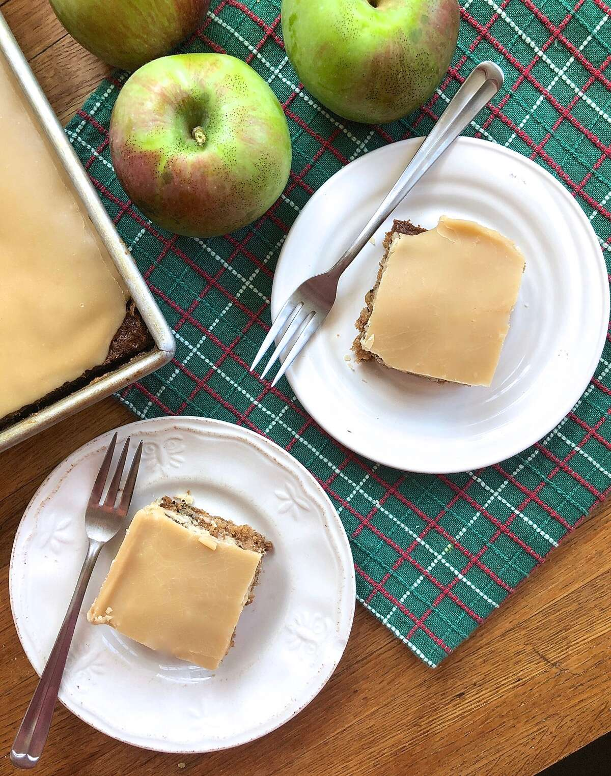 Apple cake with brown sugar frosting cut into squares and served on plates.