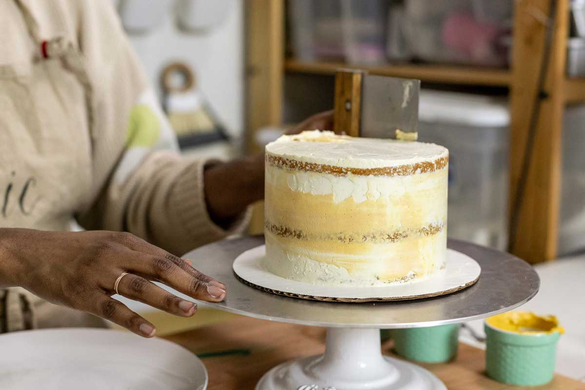 Smoothing colored frosting layer onto cake