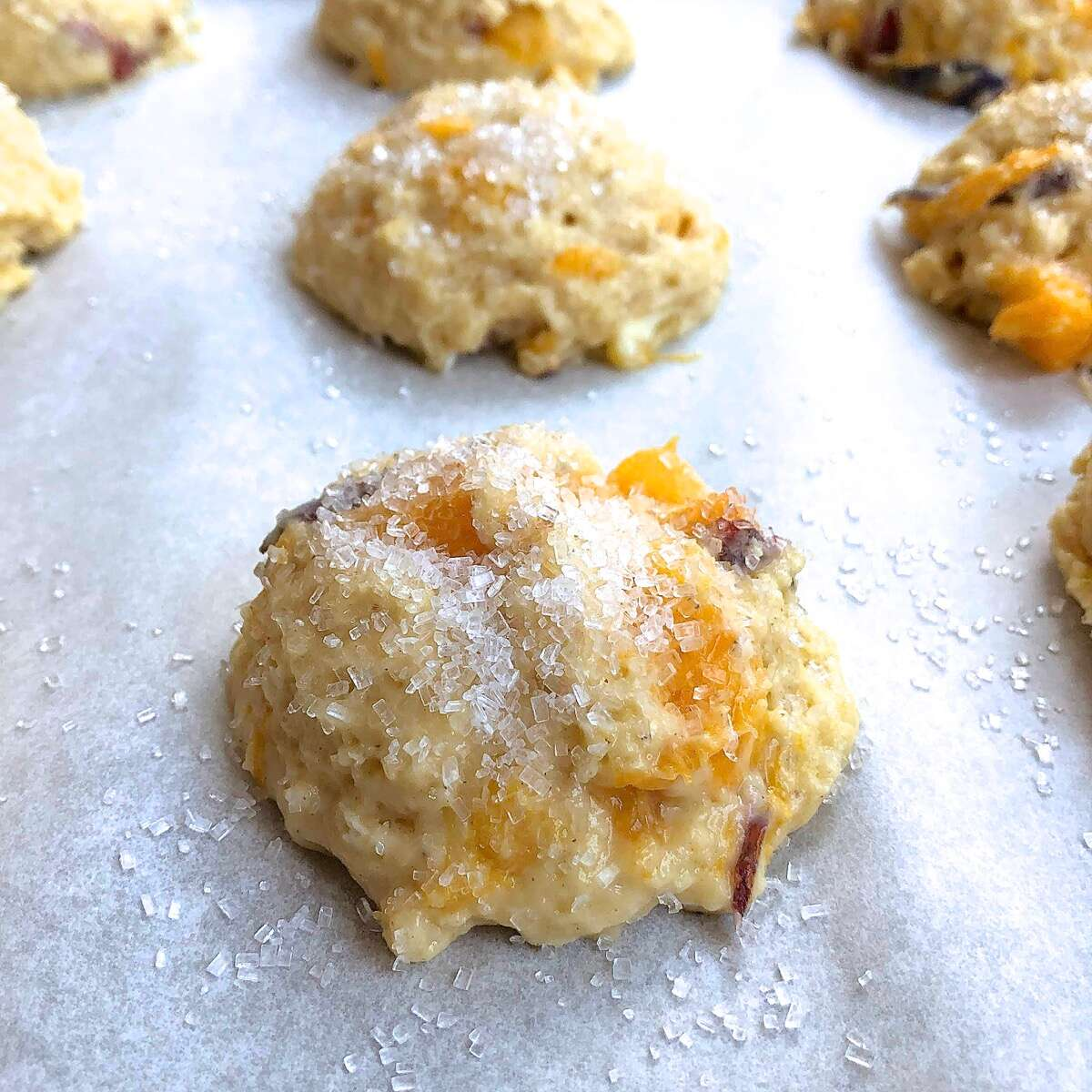 An unbaked peach scone garnished with coarse white sparkling sugar, ready to be baked.