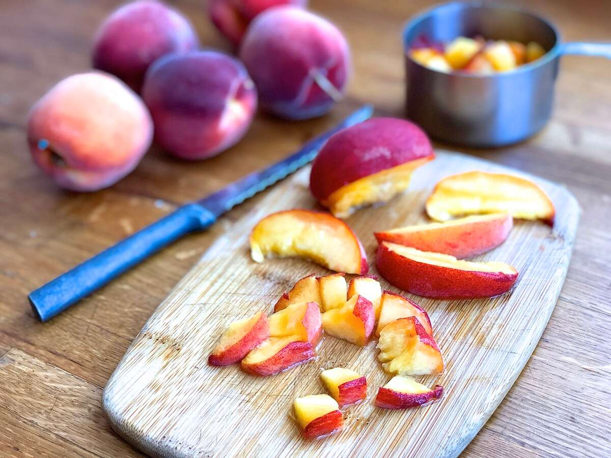 A fresh unpeeled peach cut into slices and then chunks on a cutting board.