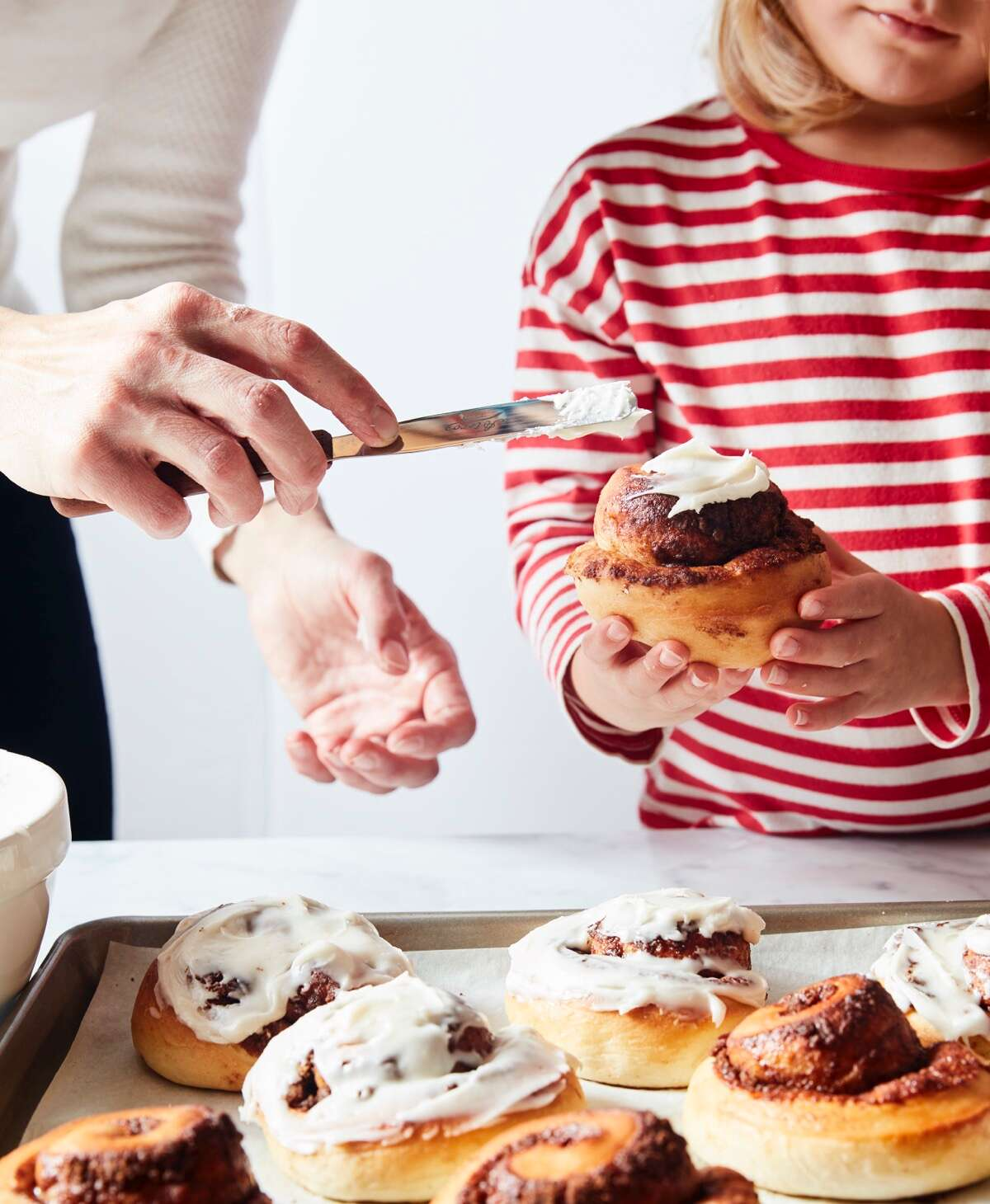 Little girl in a red-striped shirt holding a cinnamon roll while Mom frosts it with white icing.