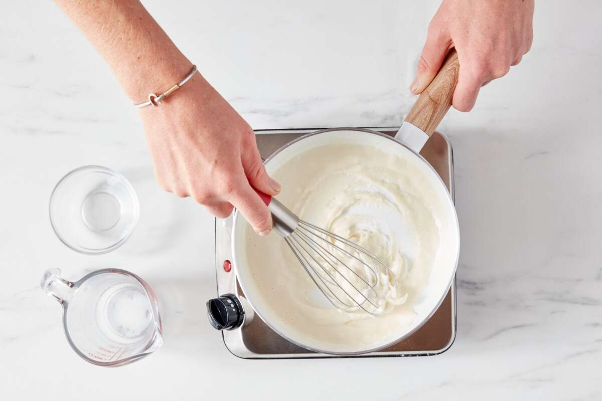 Hands using a whisk to mix flour and milk in a saucepan set over a portable burner.
