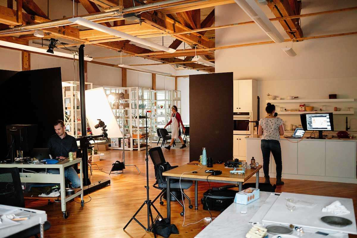 Interior of photo studio, showing photography kitchen, prop shelving, and open space with equipment and tables