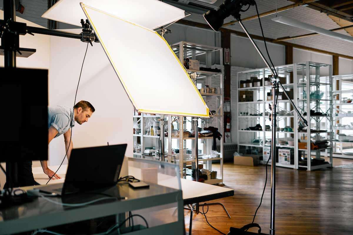 Photographer with photo and lighting equipment in studio