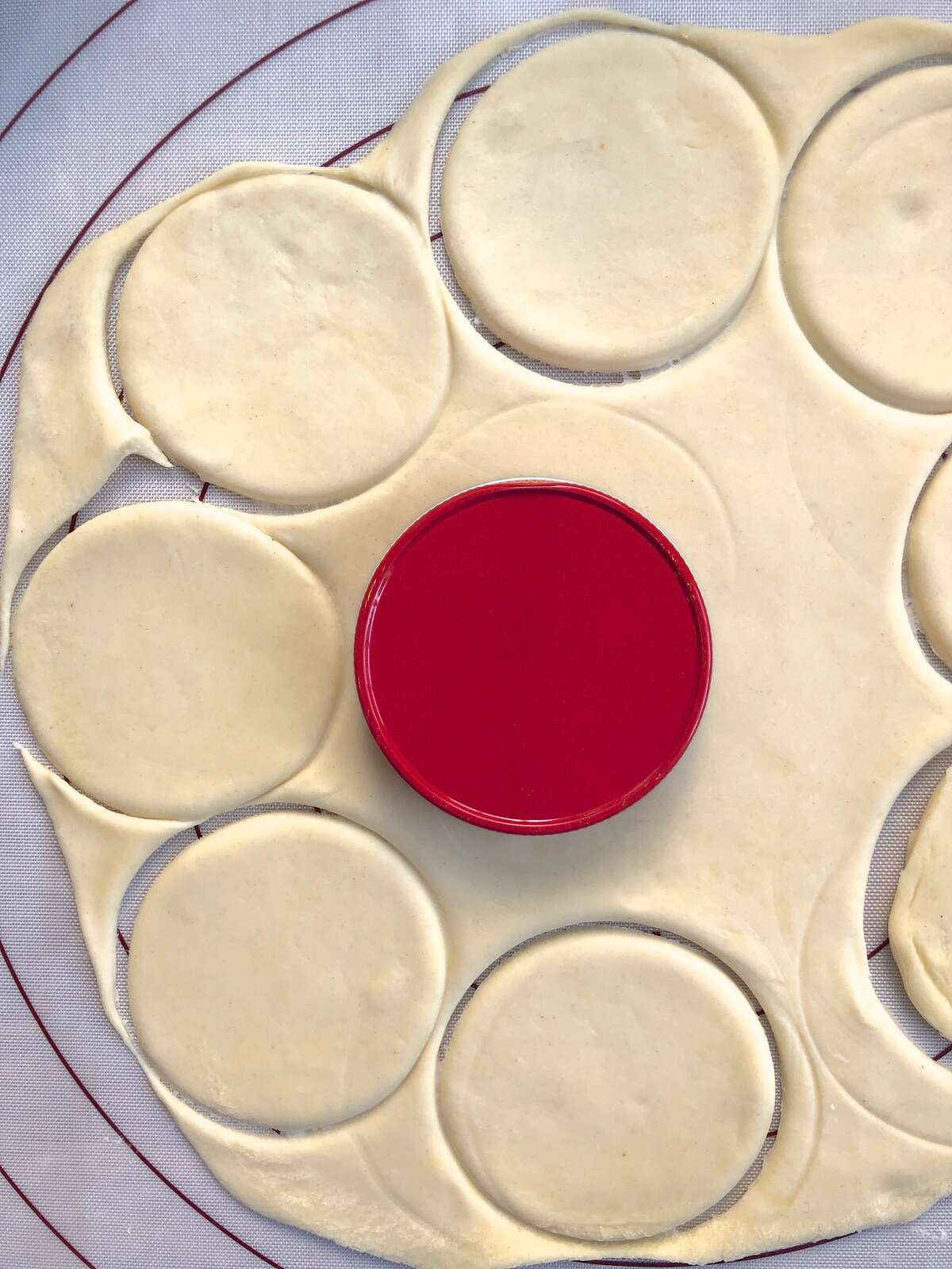 Pierogi dough rolled into a circle, and smaller circles being cut from the dough with a jar lid.