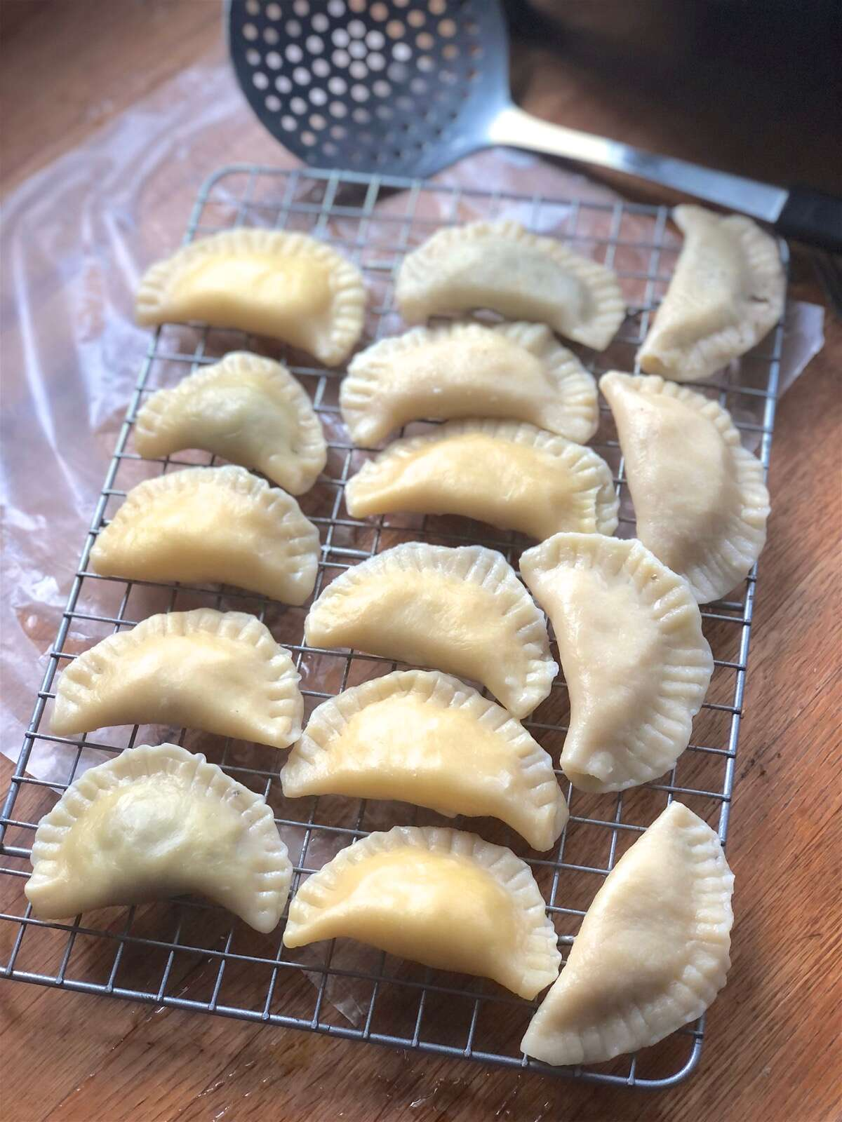Boiled pierogi cooling on a rack prior to being fried with onions.