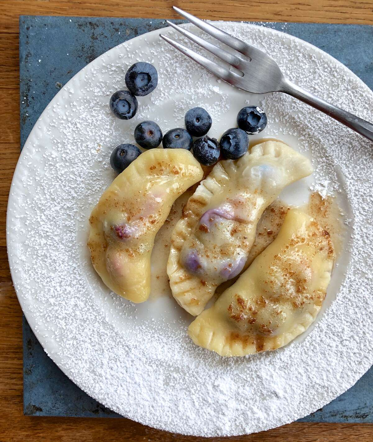 Fresh berry pierogi on a plate, drizzled with brown butter and dusted with confectioners' sugar .