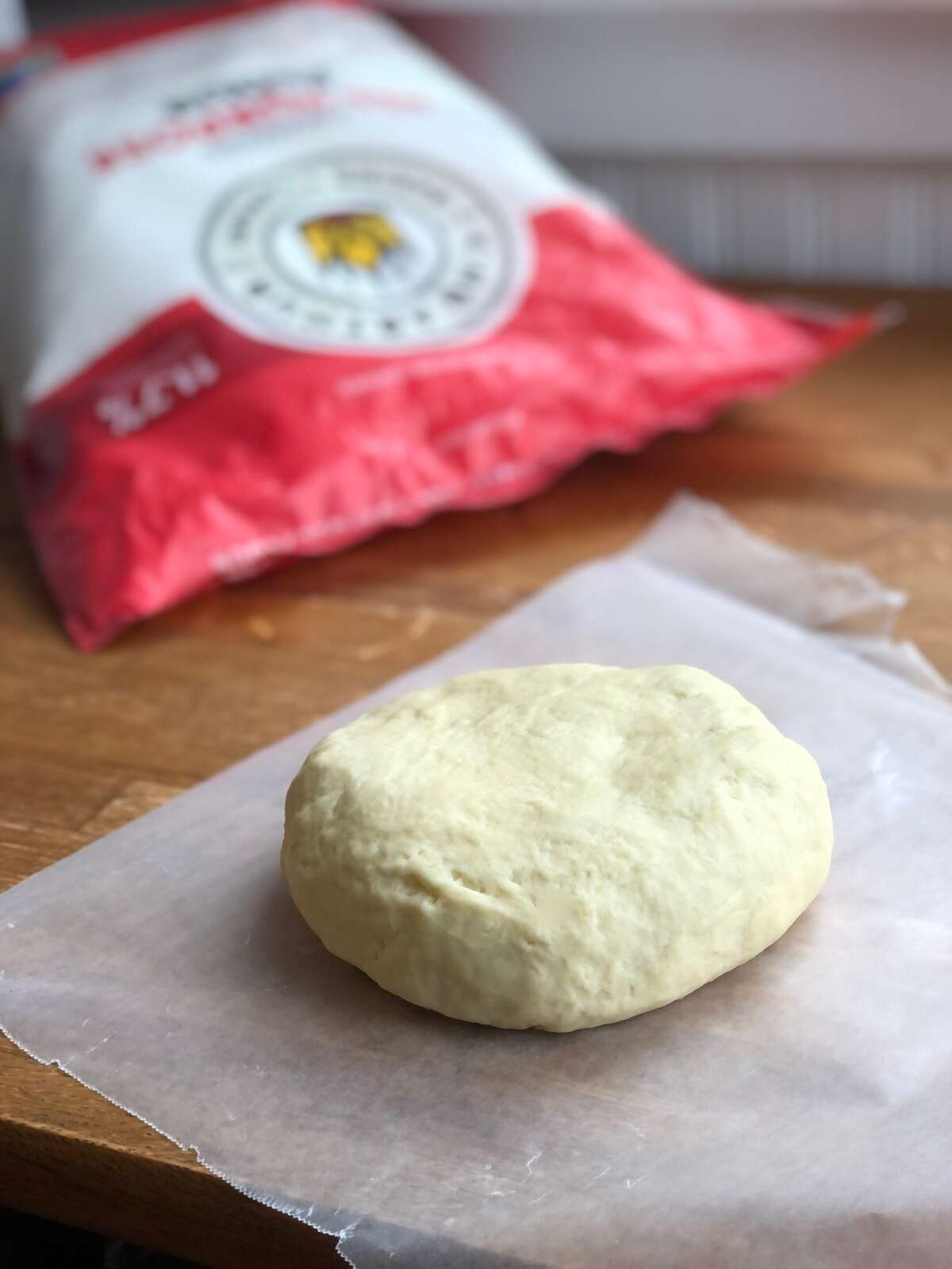 Pierogi dough flattened into a disc, ready to wrap and chill.