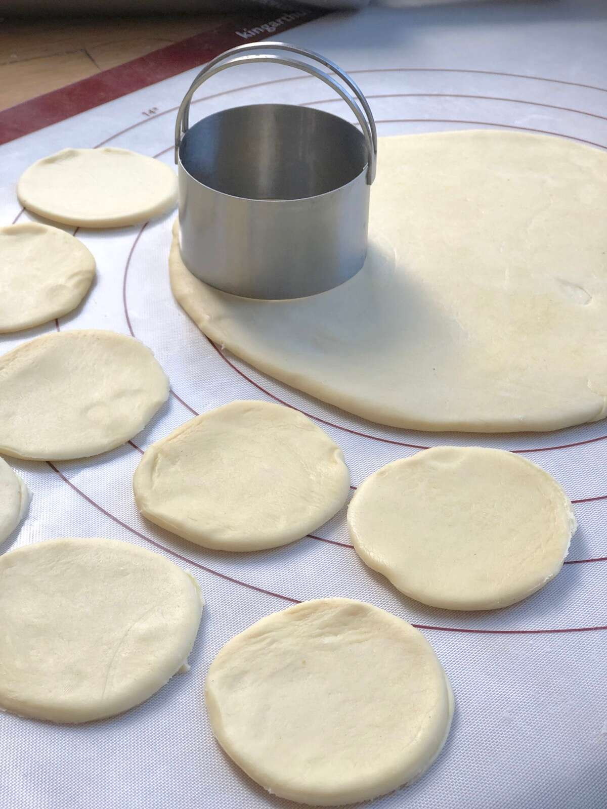 Rolled pierogi dough on a silicone mat being cut with a round biscuit cutter.