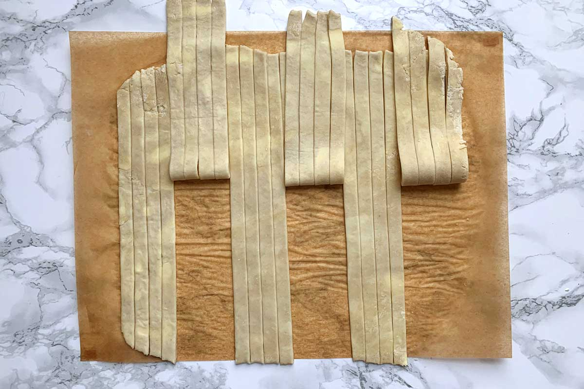 Sheet of dough cut into vertical strips, alternating between four strips pulled back and four laying flat