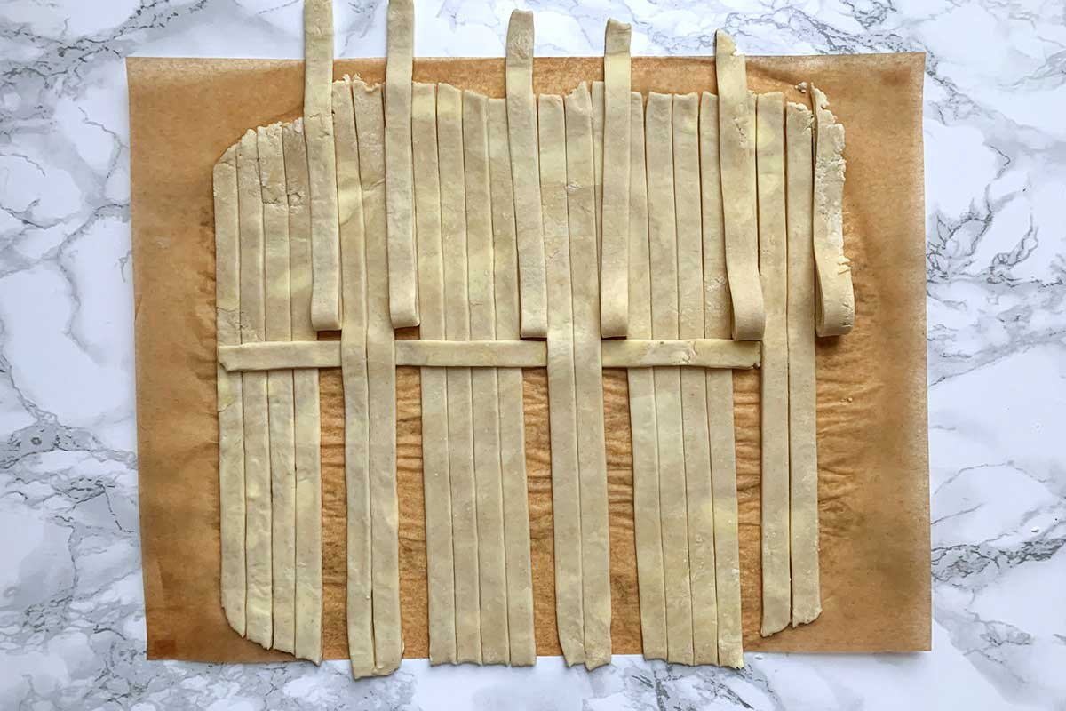 Same sheet of dough as previous image, with middle two strips in each group unfolded over horizontal strip
