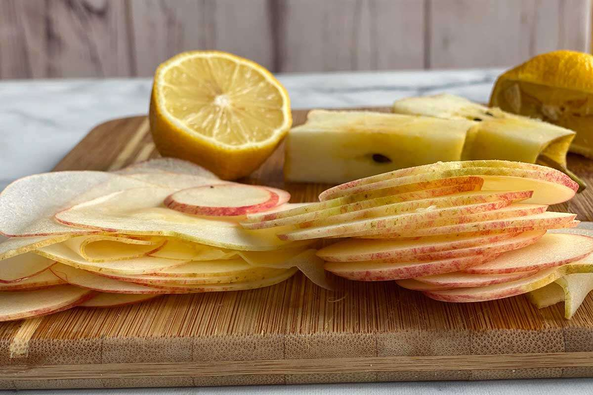 A pile of thinly sliced apple discs on a wooden cutting board next to a lemon