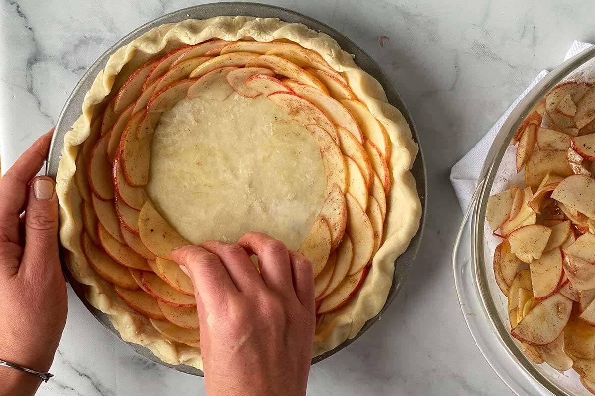 A baker assembling a rose apple pie by layering thinly sliced apples on top of one another in concentric rings