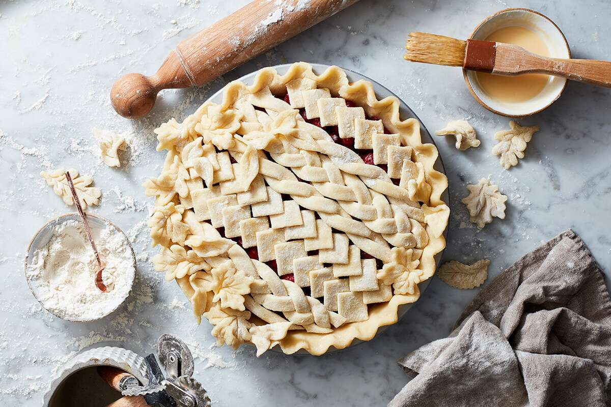 An unbaked, lattice-topped pie made with Rustic Milk Pie Dough