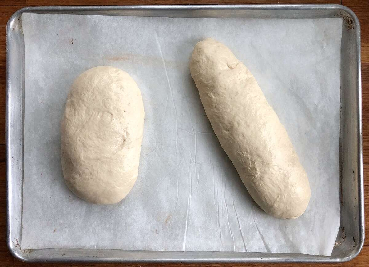 Bread dough shaped into two loaves: a fat oval and a longer loaf.