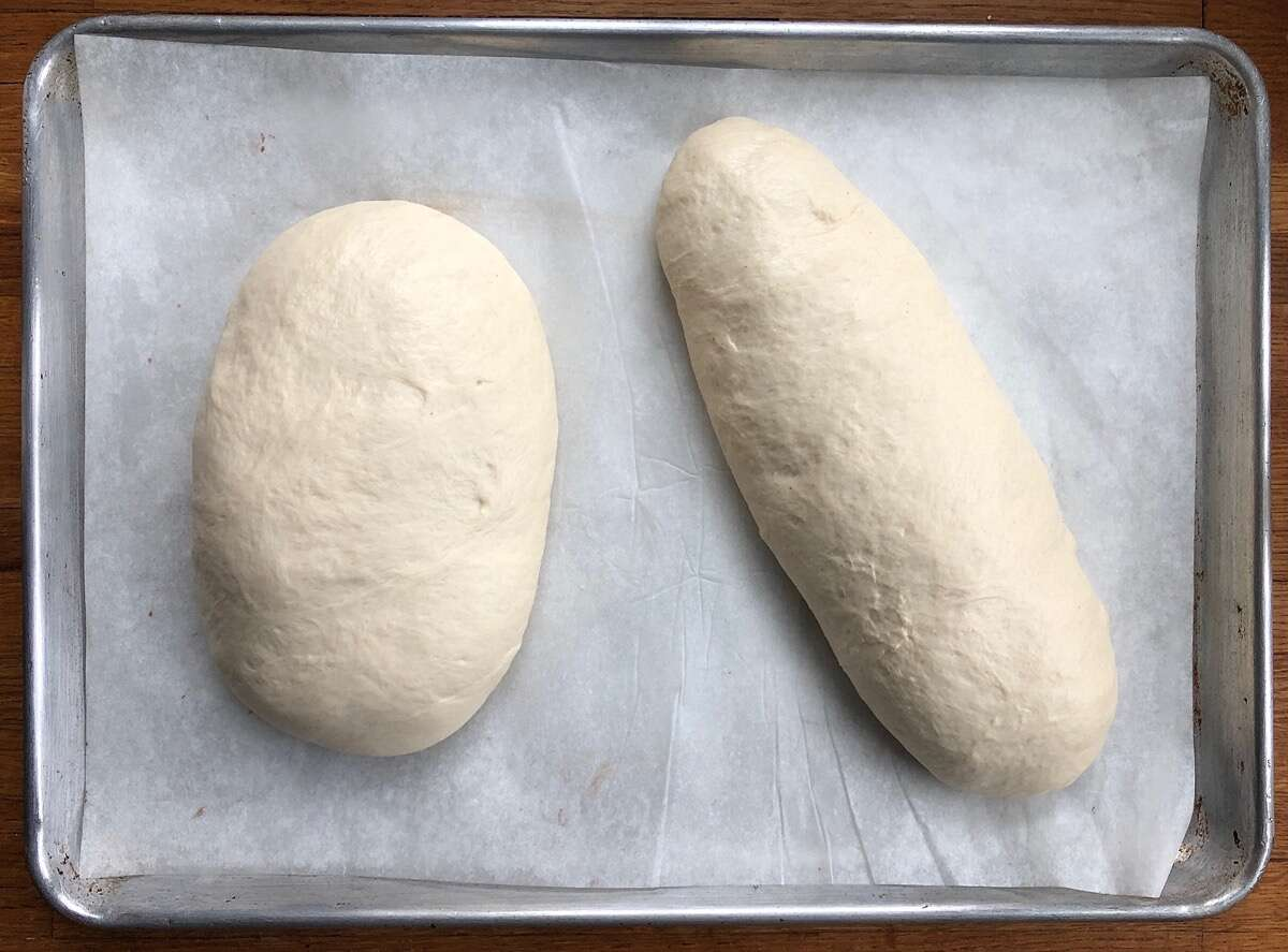 Two risen loaves of sourdough bread ready to be baked.