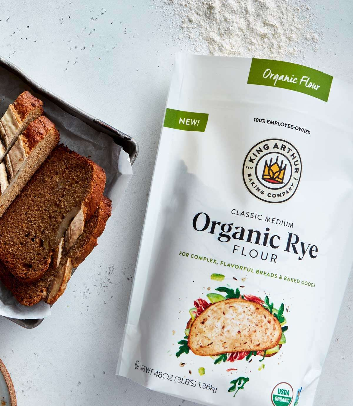 Bag of Organic Medium Rye Flour, next to a loaf of banana bread