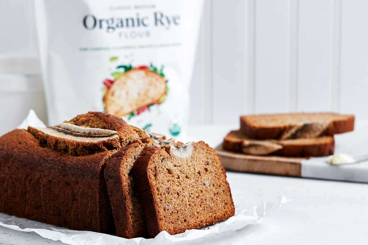 A loaf of rye banana bread next to a bag of King Arthur Organic Medium Rye Flour