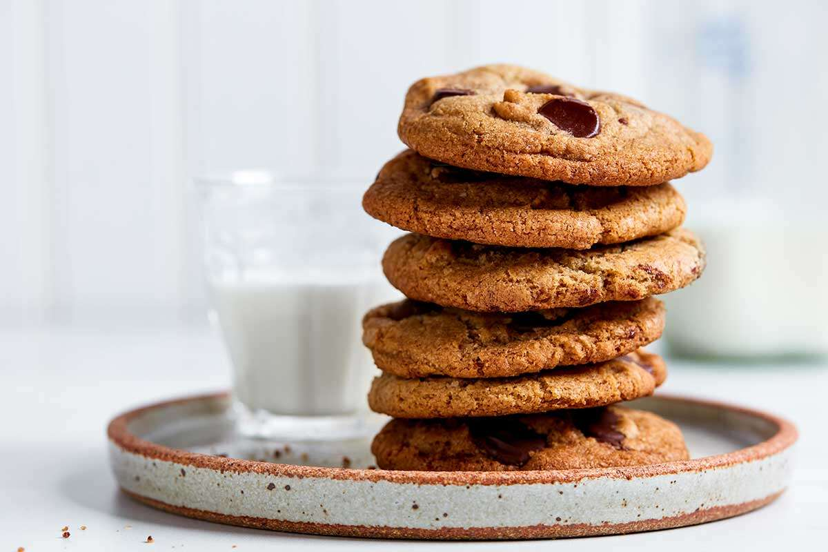 A stack of rye chocolate chip cookies on a plate next to a glass of milk