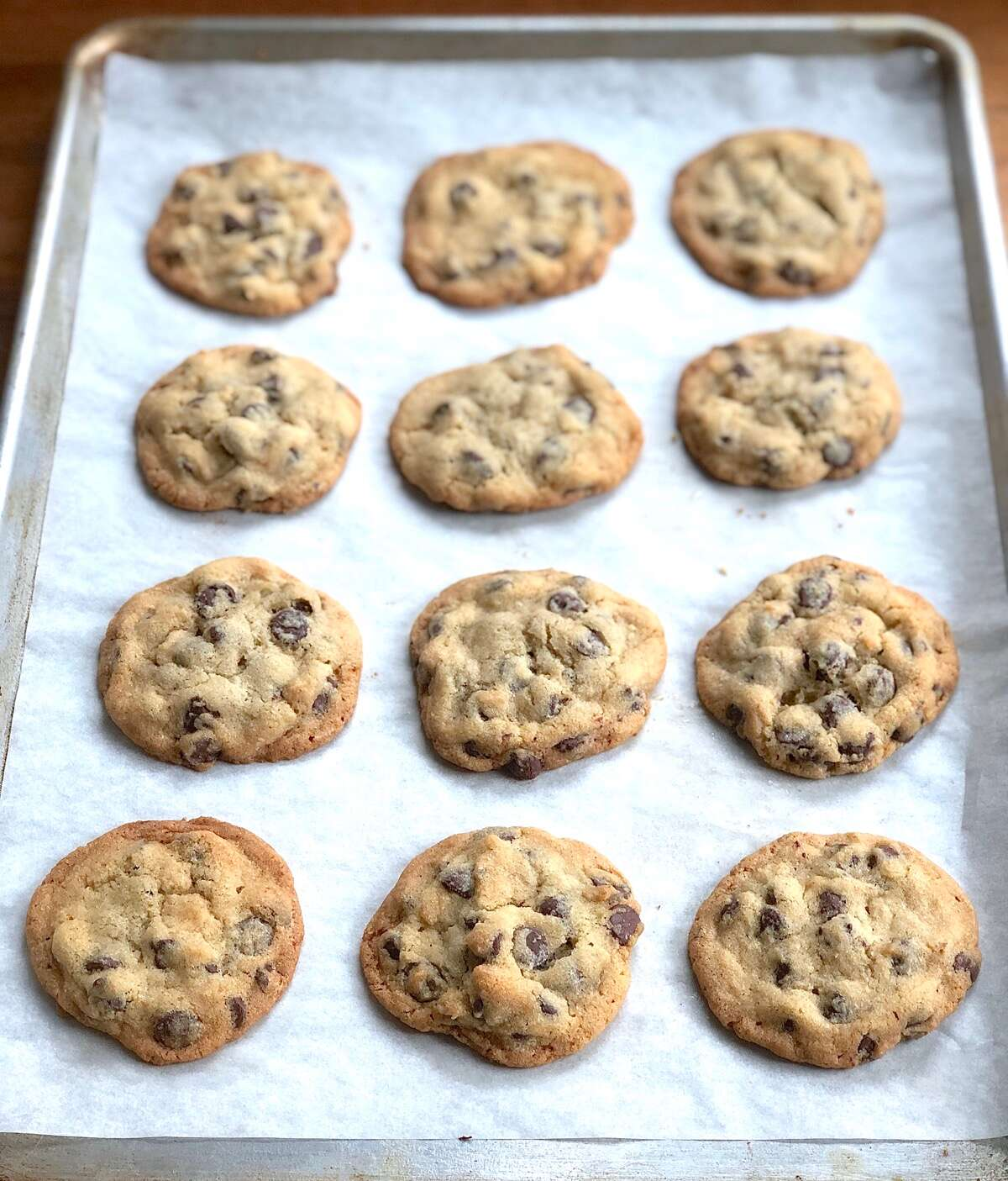 Rows of baked chocolate chip cookies on a parchment-lined baking sheet.