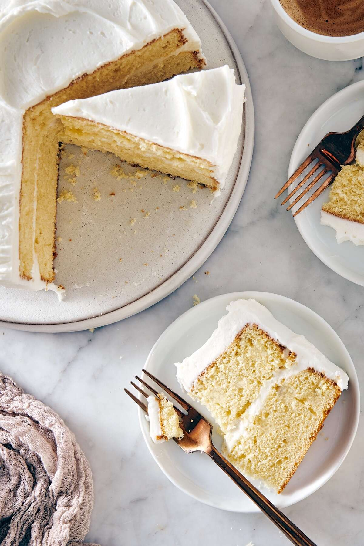 Slice of yellow layer cake with white frosting on a plate, remainder of cake on the side.er of