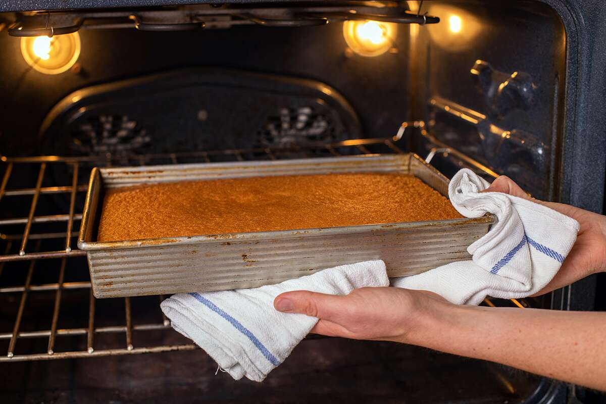 A baker pulling a vanilla sheet cake out of the oven to check for doneness