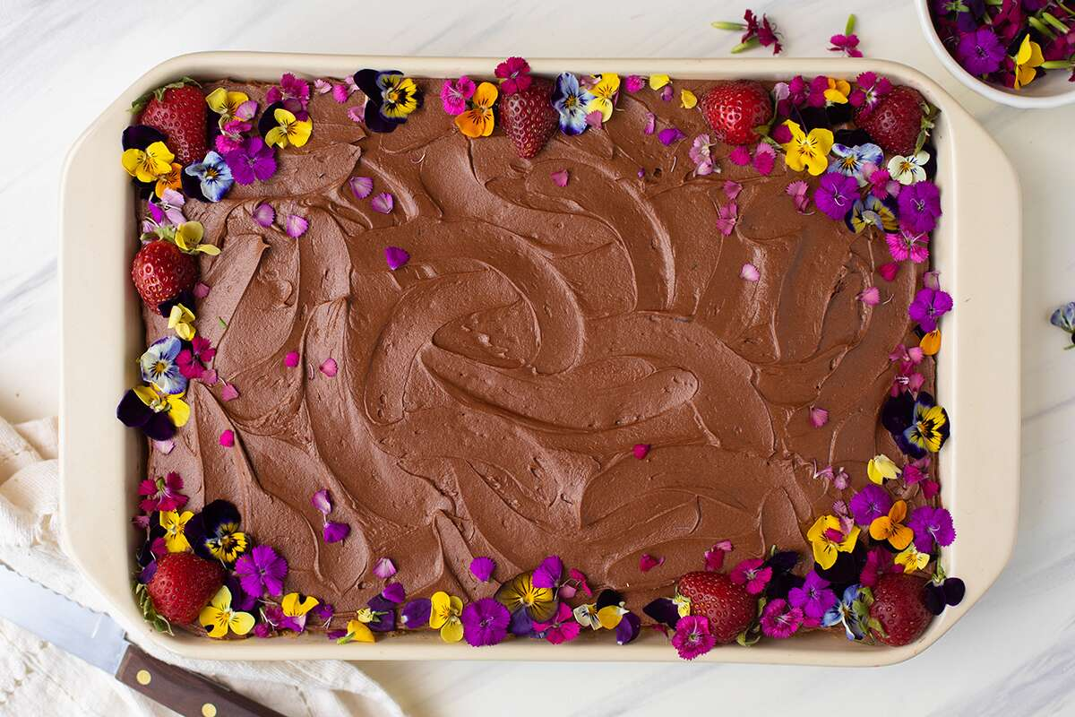 A Classic Birthday Cake baked as a sheet cake and decorated with edible flowers and strawberries
