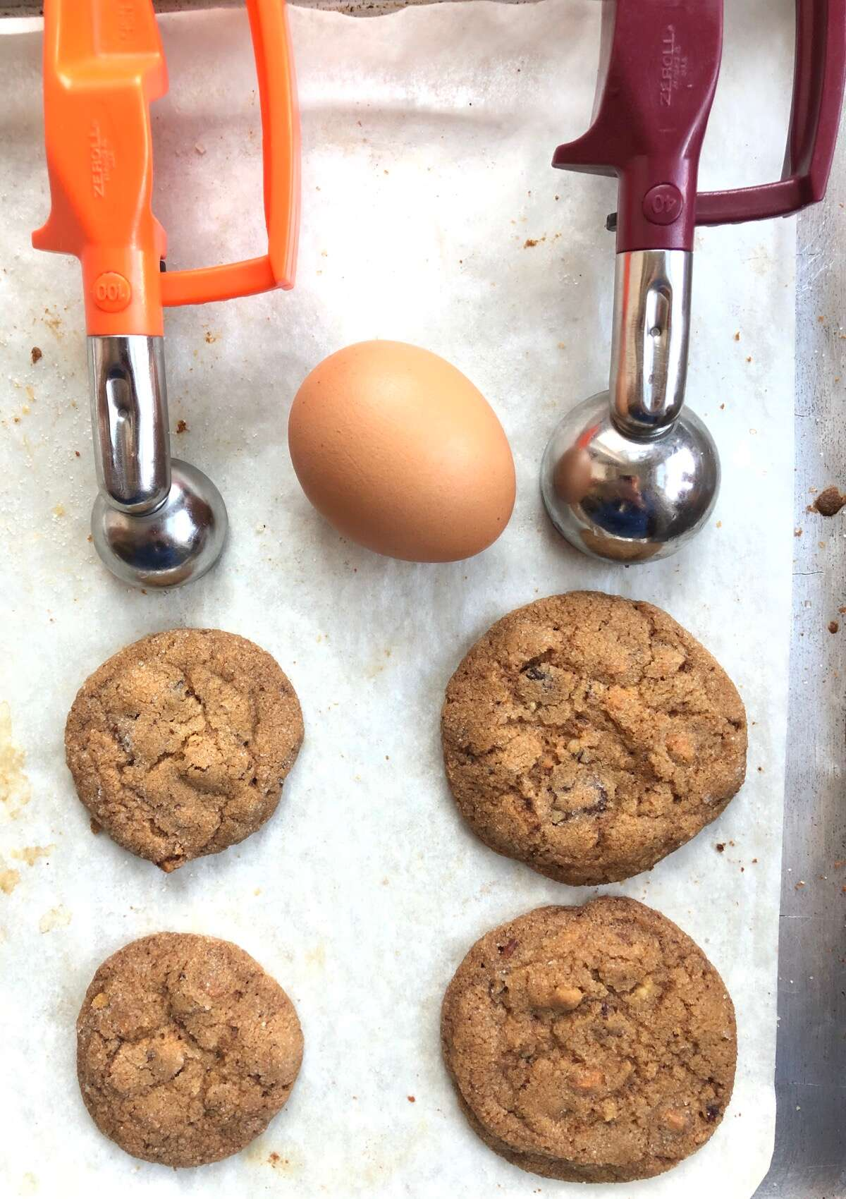 Two cookies on a baking sheet, one made with a tablespoon scoop, a smaller one made with a teaspoon scoop.