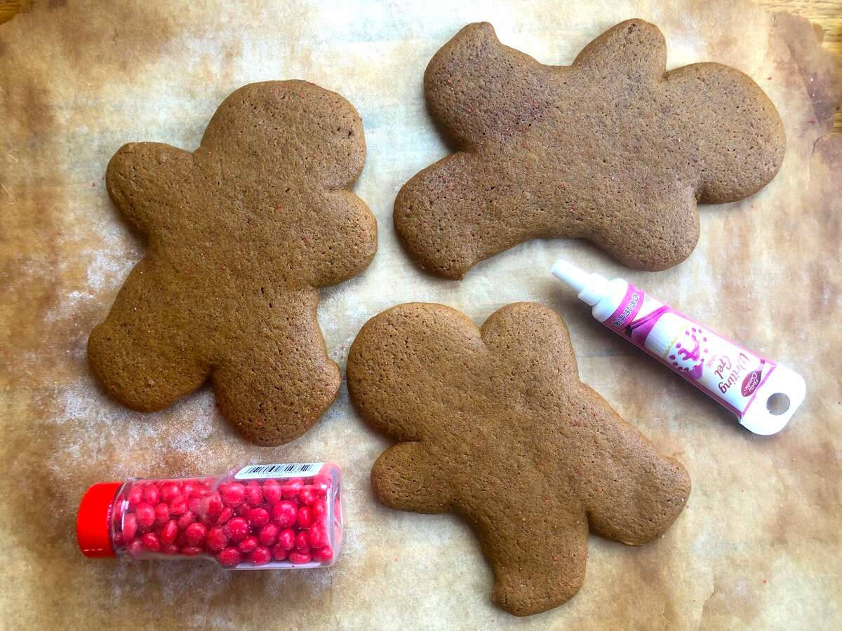 Gingerbread men on a baking sheet, no decorations, flanked with a tube of decorating gel and bottle of candy decos.