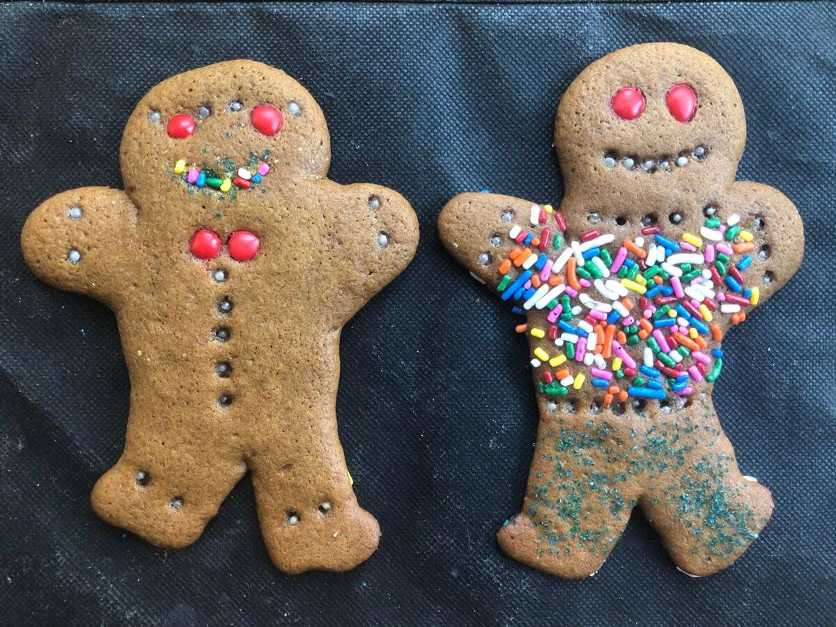 Two decorated gingerbread men on a black cloth.