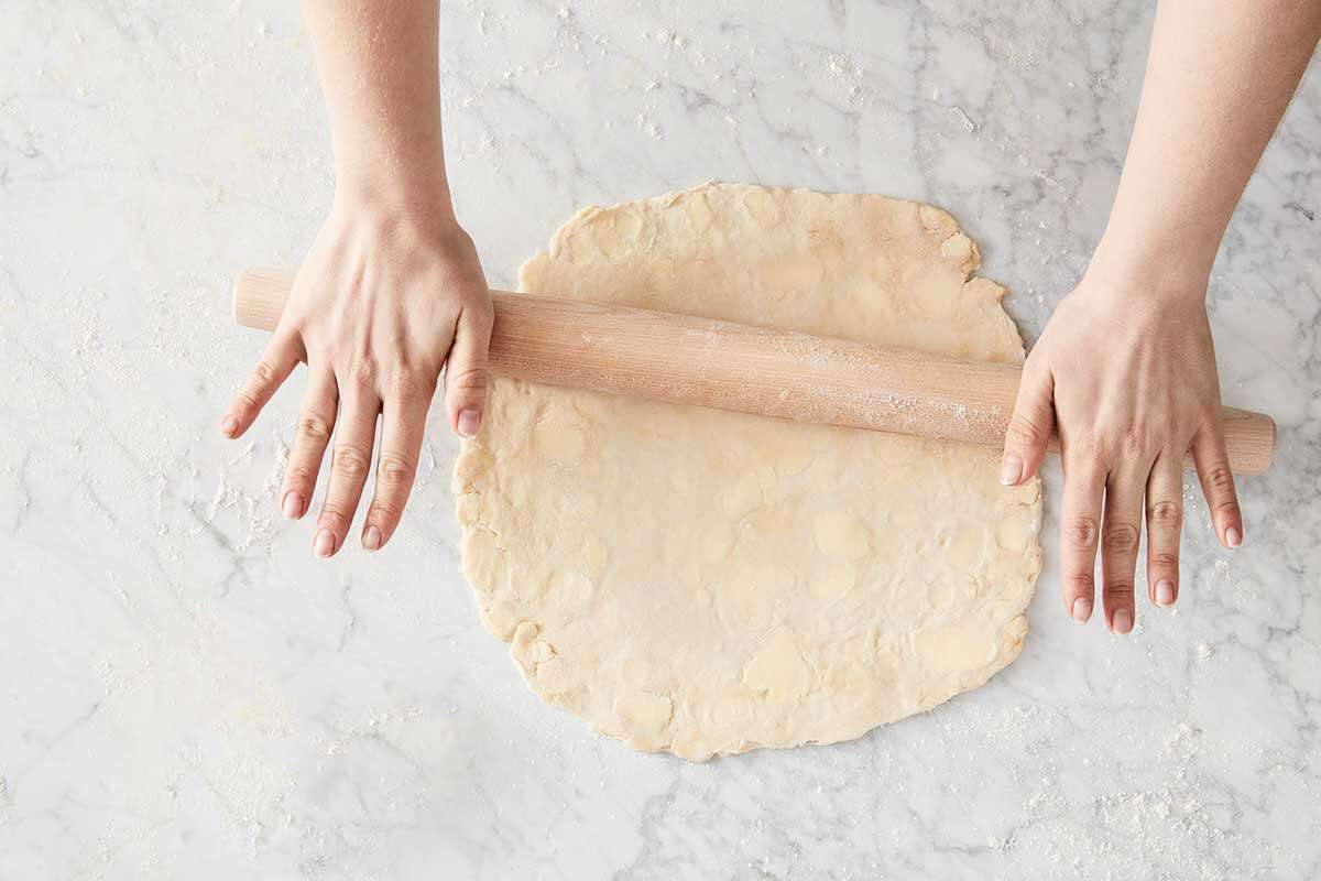 A baker rolling out a single pie crust