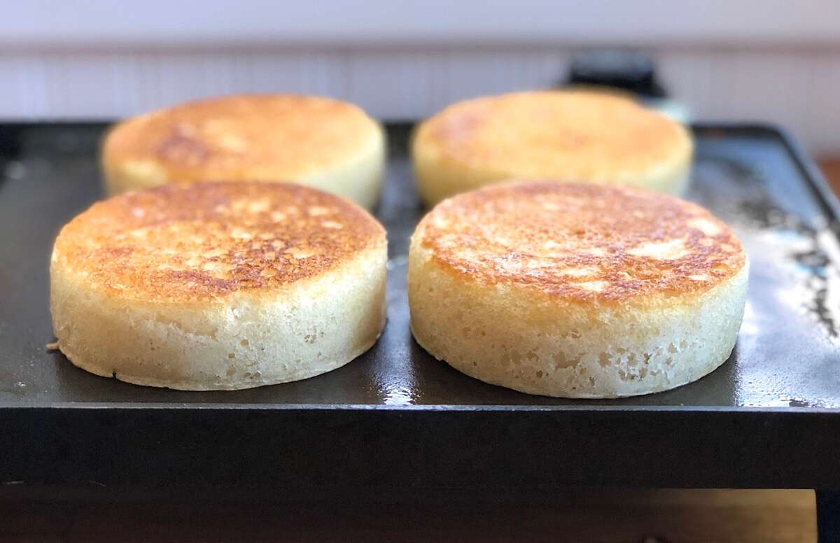 Side view of four sourdough crumpets on a griddle showing their height.