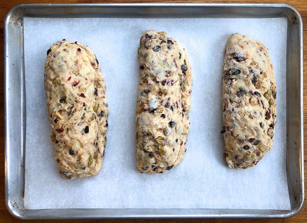 Three stollen positioned on a parchment lined baking sheet, ready to rise.