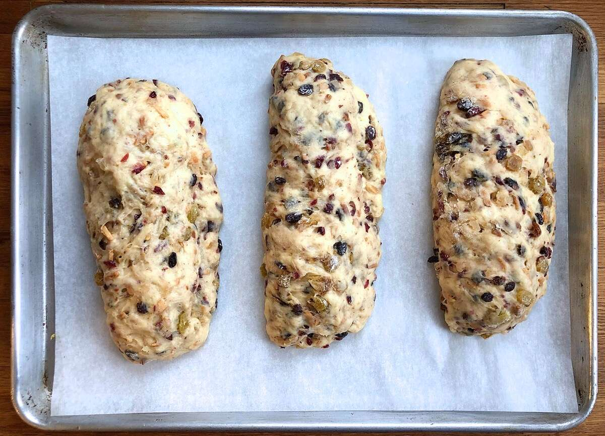 Three stollen on a baking sheet, risen and ready to bake.