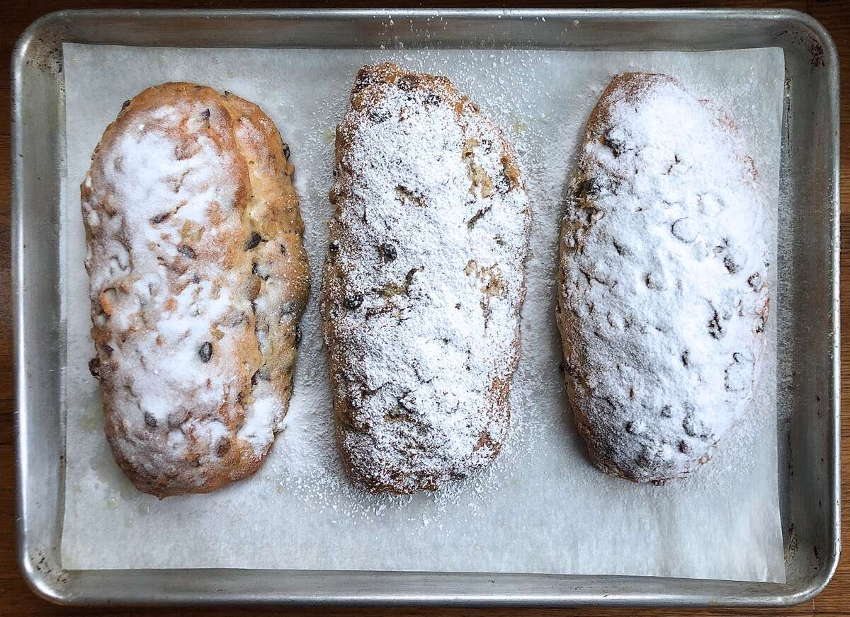 Three stollen showered with sugar, cooling on a rack.