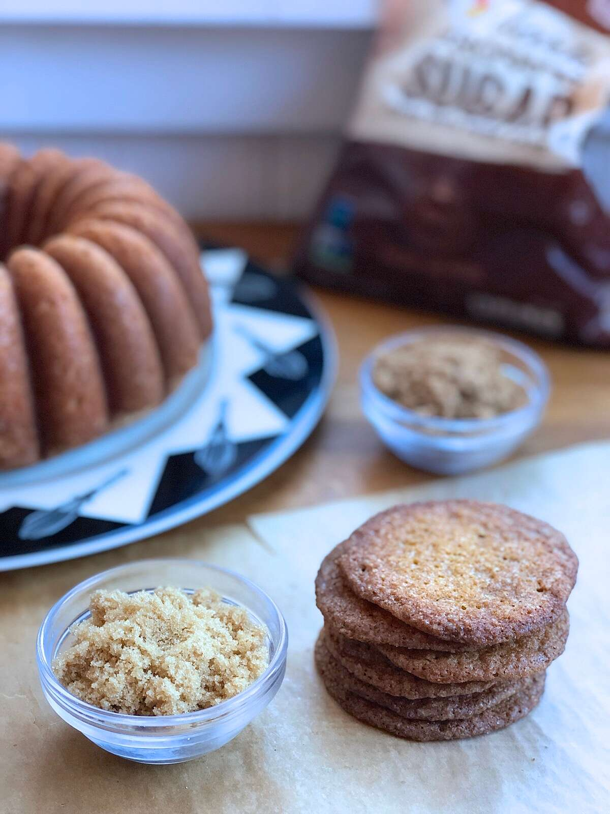 Brown sugar pound cake and buttersnap cookies on a table, bag of brown sugar in the background.