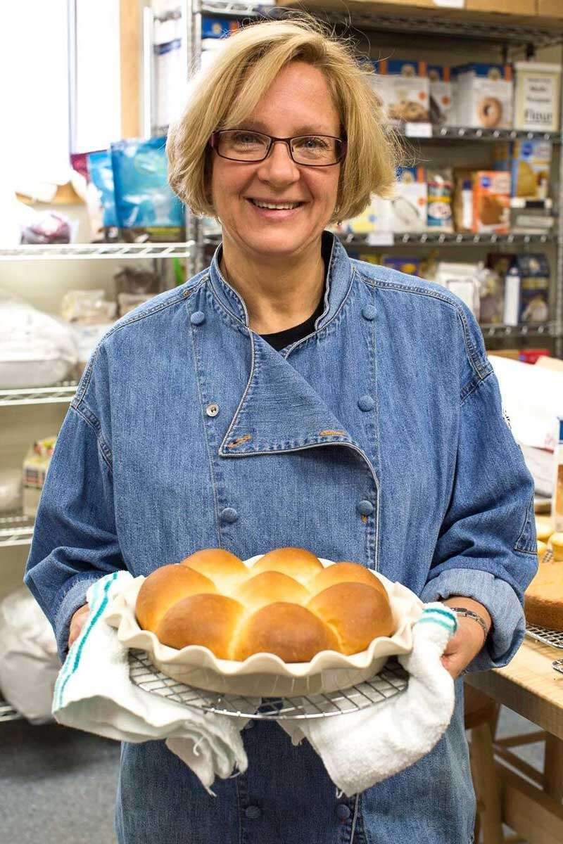Sue Gray holding a pan of rolls