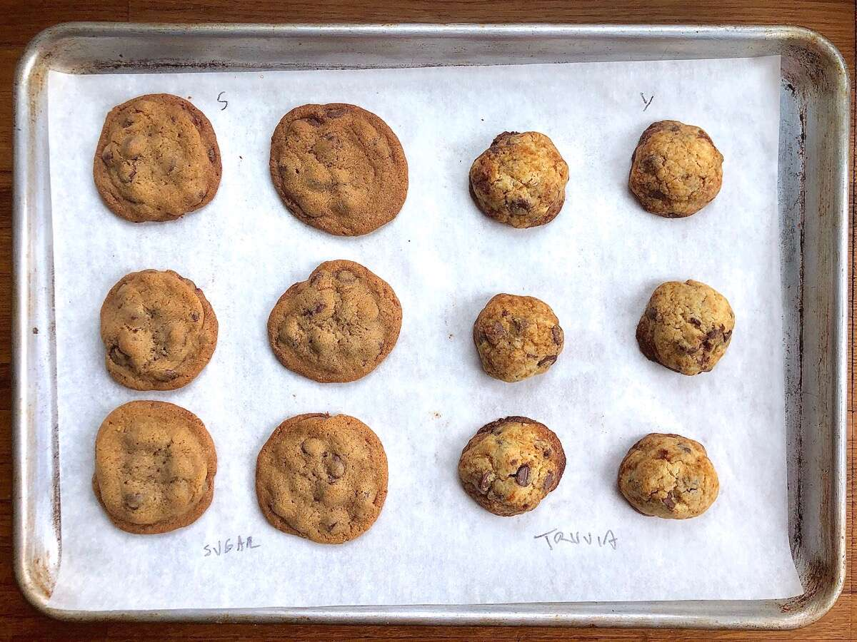 Chocolate chip cookies fresh from the oven on a baking sheet — half made with granulated sugar, half with Truvia, showing degrees of spread.